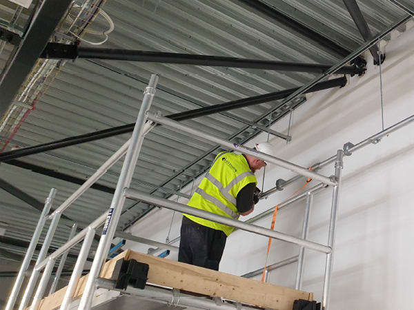 Safety trained installers using scaffold tower to install 12m lighting